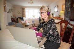 Женщина с ноутбуком, смотря онлайн содержание стоковая фотография