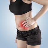 Женщина с обоими ладонь вокруг талии для того чтобы показать боль на зоне живота Стоковая Фотография