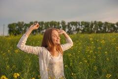 Женщина с открытыми оружиями в зеленом рапсе field на утре Стоковые Фото