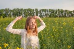 Женщина с открытыми оружиями в зеленом рапсе field на утре Стоковые Изображения RF