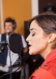 Женщина с петь закрытый глазами в студии Стоковая Фотография