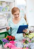 Женщина с ПК таблетки и корзина на цветочном магазине Стоковое Фото