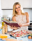 Женщина с поваренной книгой варя пиццу Стоковое Фото