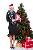 Женщина с подарком около рождественской елки стоковые фотографии rf