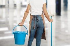 Женщина с поставками чистки в здании Стоковые Фото