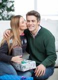 Женщина с подарками рождества целуя человека на щеке Стоковые Фотографии RF