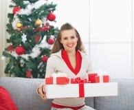 Женщина с подарком на рождество кладет в коробку около рождественской елки Стоковые Изображения