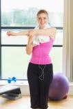 Женщина с полотенцем вокруг шеи протягивая руку в студии фитнеса Стоковое Фото