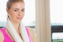 Женщина с полотенцем вокруг шеи слушая к музыке в студии фитнеса Стоковое Изображение RF