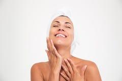 Женщина с полотенцем на голове касаясь ее fac стоковые фото