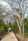 Женщина с прогулкой камеры на деревянном пути прогулки Стоковое Фото