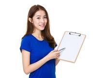 Женщина с пунктом ручки к доске сзажимом для бумаги белой бумаги Стоковая Фотография RF