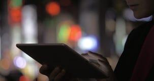Женщина с пусковой площадкой против красочного запачканного города освещает на ноче акции видеоматериалы