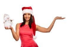 Женщина с пустой рукой в шляпе santa держит снеговик Стоковые Изображения RF