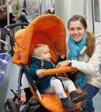 Женщина с ребенком в прогулочной коляске на метро Стоковая Фотография