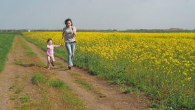 Женщина с ребенком играет в природе Счастливая семья бежит в свежем воздухе Девушка с ребенком бежит вдоль ro страны акции видеоматериалы