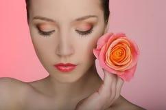 Женщина с розой закрыла ее глаза стоковые изображения rf