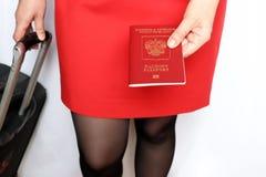 Женщина с руками чемодана русский паспорт стоковое изображение