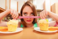 Женщина с рулеткой и тортом Дилемма диеты стоковая фотография rf