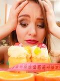 Женщина с рулеткой и тортом Дилемма диеты стоковое фото
