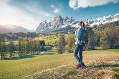 Женщина с рюкзаком в долине горы на заходе солнца весной стоковая фотография rf