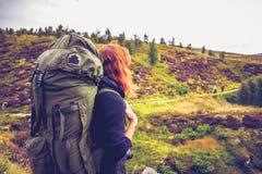 Женщина с рюкзаком наблюдая товарищеские hillwalkers в расстоянии стоковая фотография