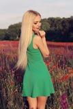 Женщина с светлыми волосами в элегантном платье представляя на поле лаванды цветения лета Стоковое Изображение RF