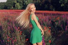 Женщина с светлыми волосами в элегантном платье представляя на поле лаванды цветения лета Стоковое Изображение