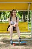 Женщина с скейтбордом и питьем стоковые изображения