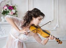 Женщина с скрипкой в белом peignoir бугинвилии обольстительно стоковые изображения rf