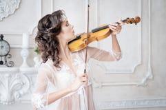 Женщина с скрипкой в белом peignoir бугинвилии обольстительно стоковое изображение