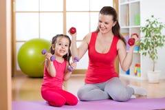 Женщина с смешным ребенком работает поднимаясь гантели Стоковые Изображения