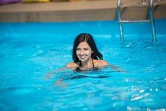 Женщина с снег-белой улыбкой плавает в бассейн с водой бирюзы в солнце на курорте, запачканной предпосылке Стоковое Фото