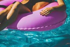 Женщина с совершенной диаграммой на кольце заплыва в бассейне стоковые фото