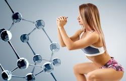 Женщина с совершенным атлетическим телом около цепи молекулы Стоковая Фотография RF