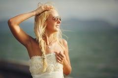 Женщина с солнечными очками и белым платьем свадьбы на предпосылке моря Стоковое Фото
