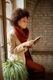Женщина с сотовым телефоном в офисе Стоковая Фотография RF