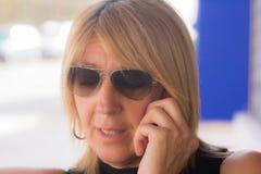 Женщина с сотовым телефоном или смартфоном пока говорящ с кто-то или сообщением стоковая фотография