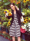 Женщина с сотовым телефоном около цветков Стоковое фото RF