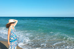 Женщина с соломенной шляпой на пляже Стоковая Фотография