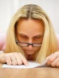Женщина с стеклами читая очень сфокусированный документ и указывать Стоковые Изображения RF