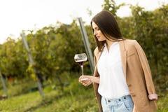 Женщина с стеклом вина в винограднике Стоковые Фотографии RF
