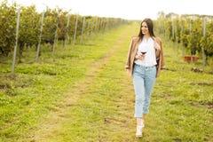Женщина с стеклом вина в винограднике Стоковое Фото
