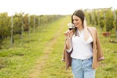 Женщина с стеклом вина в винограднике Стоковая Фотография RF