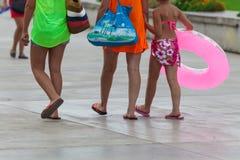 Женщина с сумкой и заплыв звенят идти к пляжу города Стоковое Изображение