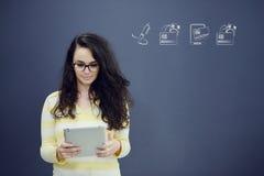 Женщина с таблеткой перед предпосылкой с вычерченными диаграммой и значками дела Стоковое Фото