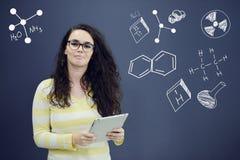 Женщина с таблеткой перед предпосылкой с вычерченными диаграммой и значками дела Стоковые Фотографии RF