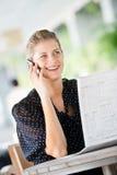 Женщина с телефоном и газетами стоковые фотографии rf