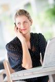 Женщина с телефоном и газетами стоковая фотография rf