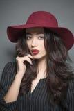 Женщина с темнотой - красная шляпа фотомодели дальше Стоковые Фото